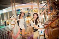 Mujeres felices que montan el equipo de los caballos del carrusel Imágenes de archivo libres de regalías