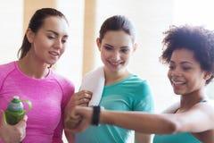 Mujeres felices que muestran tiempo en el reloj en gimnasio Imagen de archivo libre de regalías