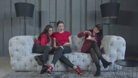 Mujeres felices que se relajan en el sofá después de fiesta de cumpleaños almacen de video