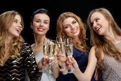 Mujeres felices que tintinean los vidrios del champán sobre negro Foto de archivo libre de regalías