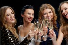 Mujeres felices que tintinean los vidrios del champán sobre negro Fotografía de archivo