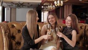 Mujeres felices que tintinean los vidrios del champán y que celebran en el restaurante metrajes