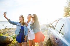 Mujeres felices que toman el selfie cerca del coche en la playa Imagen de archivo
