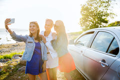 Mujeres felices que toman el selfie cerca del coche en la playa Imágenes de archivo libres de regalías