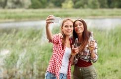Mujeres felices que toman el selfie por smartphone al aire libre Imagenes de archivo