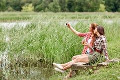 Mujeres felices que toman el selfie por smartphone al aire libre Imagen de archivo