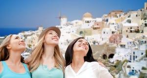 Mujeres felices sobre fondo de la isla del santorini Foto de archivo