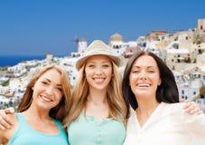 Mujeres felices sobre fondo de la isla del santorini Imágenes de archivo libres de regalías