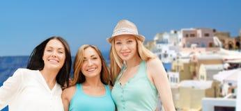Mujeres felices sobre fondo de la isla del santorini Imagen de archivo libre de regalías