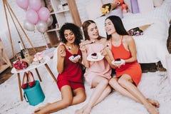 Mujeres felices Stting en piso con la torta en las placas foto de archivo