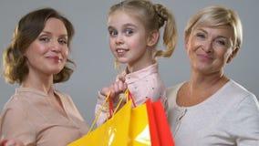 Mujeres felices y niño que sostienen los bolsos de compras, sonriendo en la cámara, descuentos del día de fiesta almacen de video