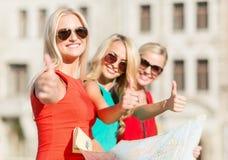 Mujeres hermosas con el mapa turístico en la ciudad Foto de archivo libre de regalías