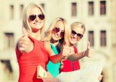 Mujeres hermosas con el mapa turístico en la ciudad Imagen de archivo libre de regalías