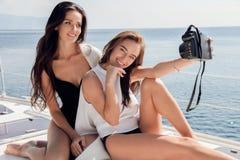 Mujeres hermosas con el pelo oscuro que se relaja en el yate en el mar abierto Imagen de archivo libre de regalías