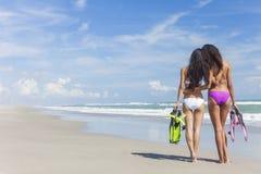 Mujeres hermosas del bikini de la vista posterior en la playa Foto de archivo libre de regalías