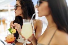 Mujeres hermosas en la playa que gozan de los cócteles Foto de archivo libre de regalías