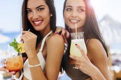 Mujeres hermosas en la playa que gozan de los cócteles Fotografía de archivo libre de regalías