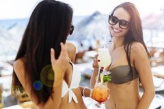 Mujeres hermosas en la playa que gozan de los cócteles Fotos de archivo