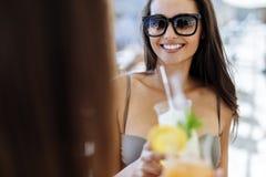 Mujeres hermosas en la playa que gozan de los cócteles Imagen de archivo libre de regalías