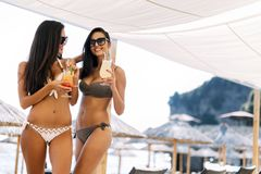 Mujeres hermosas en la playa que gozan de los cócteles Imagenes de archivo