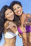 Mujeres hermosas en los bikiníes que bailan en la playa asoleada imagen de archivo