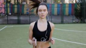 Mujeres hermosas felices que corren en los auriculares almacen de video
