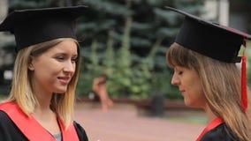 Mujeres hermosas jovenes en vestidos académicos que charlan cerca de la universidad, graduación almacen de video