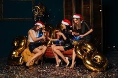 Mujeres hermosas que abren los regalos de la Navidad Fotografía de archivo libre de regalías