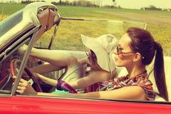 Mujeres hermosas que conducen accesoriess que llevan de un vintage retro rojo del coche Imagenes de archivo