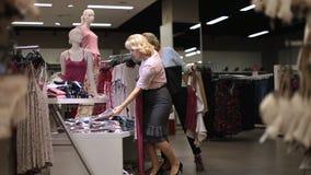 Mujeres hermosas que hacen compras para la ropa en la tienda almacen de video