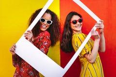 Mujeres hermosas que llevan a cabo un marco en blanco de la foto foto de archivo libre de regalías