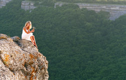 Mujeres hermosas que se sientan en tapa de la montaña Fotos de archivo