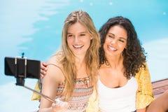 Mujeres hermosas que toman un selfie por la piscina Fotos de archivo