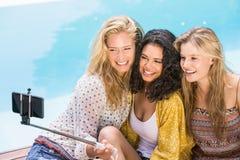 Mujeres hermosas que toman un selfie por la piscina Fotografía de archivo