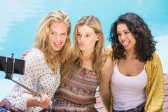 Mujeres hermosas que toman un selfie por la piscina Foto de archivo libre de regalías
