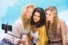 Mujeres hermosas que toman un selfie por la piscina Foto de archivo