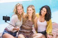 Mujeres hermosas que toman un selfie por la piscina Imágenes de archivo libres de regalías