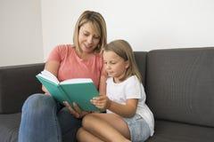 Mujeres hermosas y felices jovenes que se sientan así como sus 7 años adorables de la muchacha del libro de lectura rubio adorabl Fotografía de archivo libre de regalías