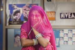 Mujeres hindúes cubiertas por una bufanda violeta de un fam conservador delante de una cartelera por completo de imágenes de muje Imagen de archivo