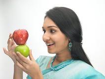 Mujeres indias con la manzana roja y verde Fotos de archivo