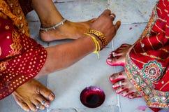 Mujeres indias que adornan pies con el tinte rojo brillante Alta mahavar imagenes de archivo