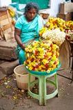 Mujeres indias que venden la guirnalda colorida de la flor en el lugar del mercado callejero para la ceremonia de la religión Foto de archivo libre de regalías