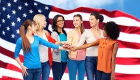 Mujeres internacionales unidas sobre bandera americana Fotos de archivo