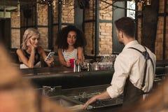 Mujeres jovenes agradables que son servidas por un camarero Imágenes de archivo libres de regalías