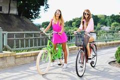 Mujeres jovenes atractivas en bicicletas - retrato al aire libre de la moda Fotos de archivo libres de regalías