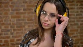 Mujeres jovenes atractivas hermosas en los auriculares que miran con confianza en la cámara, vidrios conmovedores, centelleo, fem metrajes