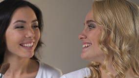 Mujeres jovenes atractivas que aplican el polvo, sonriendo sinceramente, tendencias de la belleza, maquillaje almacen de video