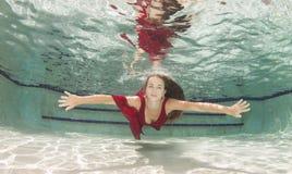 Mujeres jovenes atractivas que modelan los diversos equipos en una piscina Imágenes de archivo libres de regalías