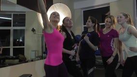 Mujeres jovenes atractivas que toman un selfie con el teléfono elegante en gimnasio almacen de metraje de vídeo