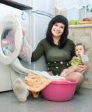Mujer con el bebé que introduce la ropa a la lavadora Fotos de archivo libres de regalías